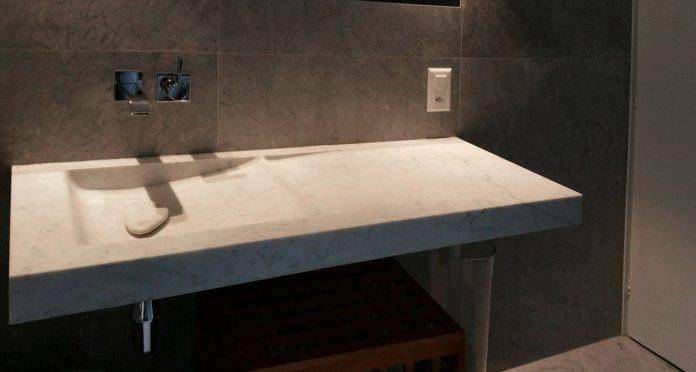 Realizzazione Bagno in Marmo su Misura Lavandino Bianco Carrara e Rivestimento parete in Grigio – Lugano, Svizzera