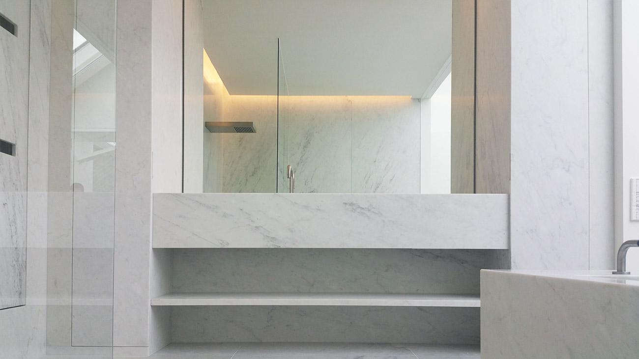 Bagno in marmo realizzato su misura con rivestimenti in marmo bianco e top lavabo