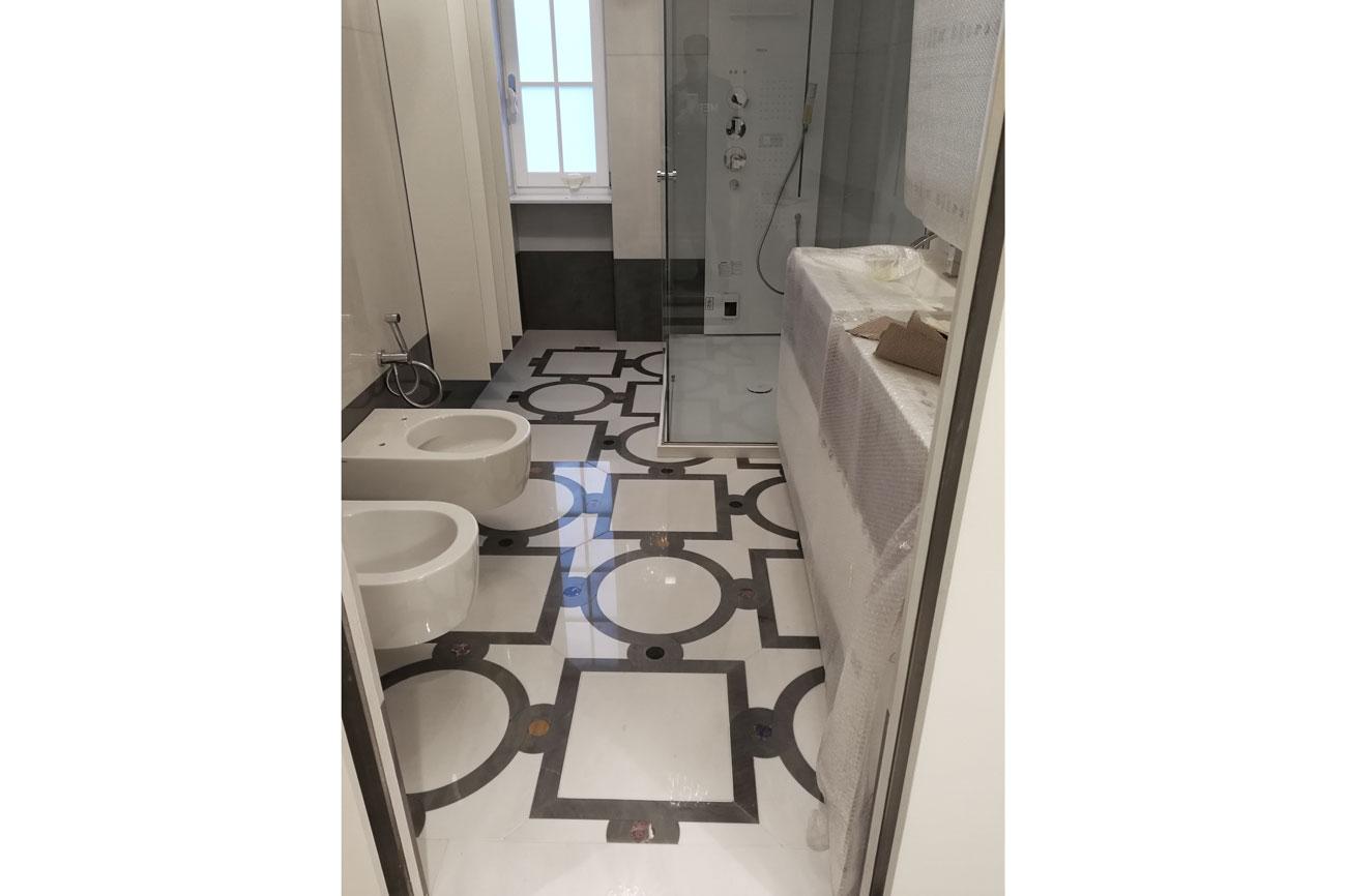 Bagno con pavimento intarsiato in marmo