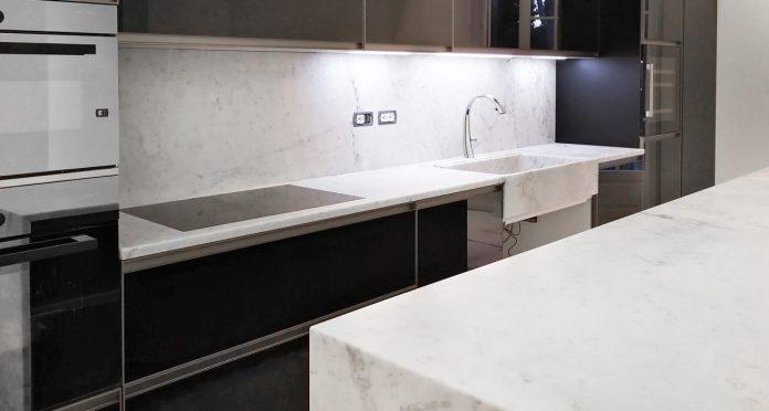 Appartamento con arredamento in marmo su misura: isola cucina, bagni, pavimento e camino